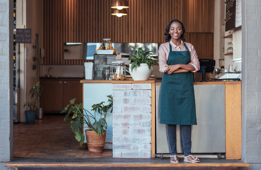 smiling woman entrepreneur standing welcomingly in front of her cafe